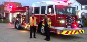 Firetruck with firemen in front of it